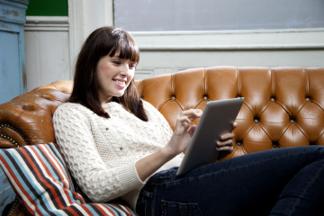 Happy and attractive young woman using a tablet computer on couch